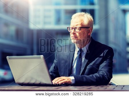 business, technology and people concept - senior businessman with laptop computer at city street cafe