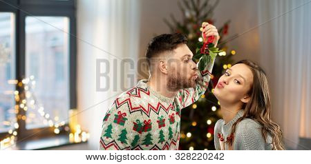 poster of people and holiday traditions concept - portrait of happy couple in ugly sweaters kissing under mistletoe over home and christmas tree lights on background