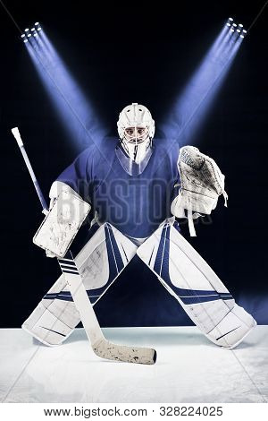Hockey Goalie Stands In The Spotlight Ready To Catch The Puck.hockey Goalie In Complete Hockey Gear