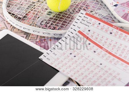 Digital Tablet, Betting Lists, Tennis Racket And Ball On Euro And Dollar Banknotes, Sports Betting C