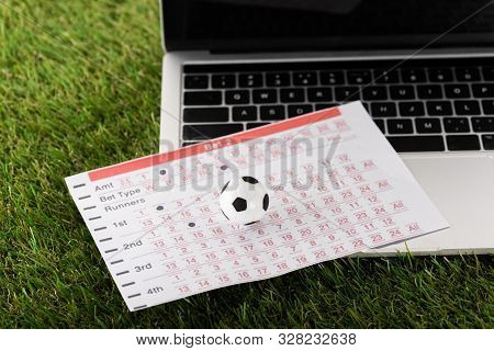 Toy Soccer Ball And Betting List Near Laptop On Green Grass, Sports Betting Concept