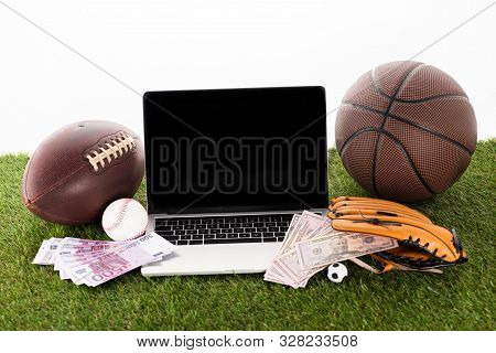 Laptop Near Sports Balls, Baseball Glove, Euro And Dollar Banknotes On Green Grass Isolated On White