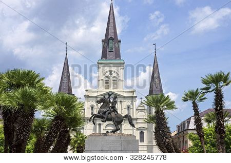 Historic Cathedral And Monument Of Andrew Jackson Atop Horse Framed By Palm Trees At Jackson Square