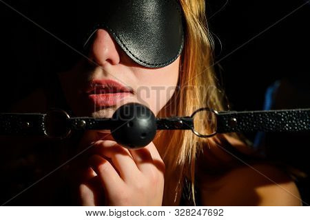 A Man Dominates And Puts A Gag In Her Mouth. Bdsm Concept. Portrait Of A Woman In Seductive Underwea