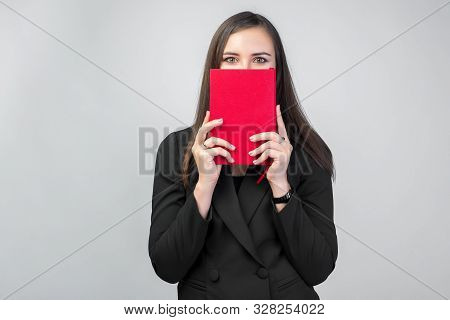 A Young Brunette Girl In A Business Suit Holds A Red Notebook In Front Of Her Face, White Background