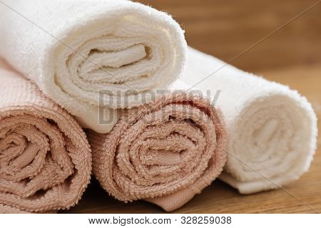 Folded Bath Towels Pink And White Colored On Wooden Table For Hotel Spa. Clean Fluffy Towels. Close