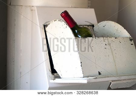 Close-up Indoor Shot Of A Wine Bottle In A Garbage Chute