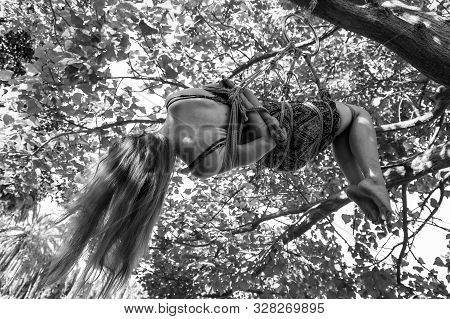 A Young Long Haired Girl Is Hanging From A Tree Tied Up With Ropes In Shibari Fetish Practice - Blac