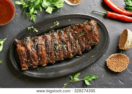 Grilled Spare Ribs On Plate Over Black Stone Background. Tasty Bbq Meat. Top View