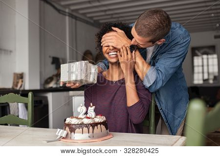 Man giving present to his beloved girlfriend on birthday with cake on table. Cheerful african woman surprised by man during her 25th birthday. Guy covering girl eyes while surprising her with present.