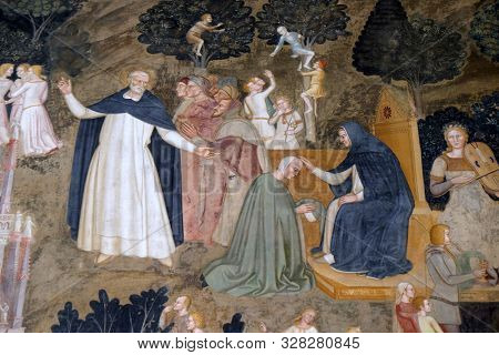 FLORENCE, ITALY - JANUARY 10, 2019: Saint Dominic showing the way to Heaven, detail of the Active and Triumphant Church, fresco by Andrea Di Bonaiuto, Santa Maria Novella church in Florence