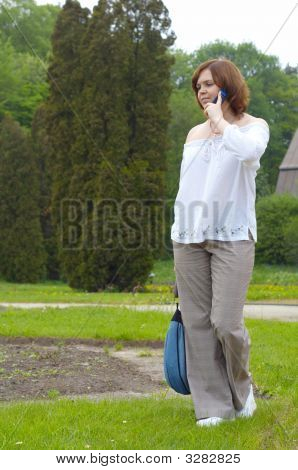 Young Girl With Telephone In A Park