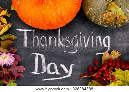 Words Thanksgiving Day Written On Blackboard With Pumpkins, Autumn Leaves And Viburnum Berries. Clos