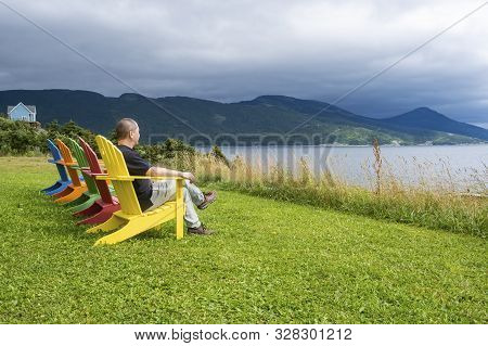 A Man Sitting In The First Of A Row Of Bright And Colorful Adirondack Chairs Facing Bonne Bay On A C