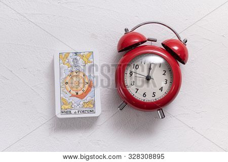 Kurgan, September 1, 2019: Wheel Of Fortune Tarot Card And Red Alarm Clock On White Stone Table Back