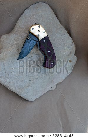 A Partially Folded Liner Lock Knife Sitting On A Flat Rock. Damascus Blade, Purple Heart Handle, Qua