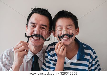 Happy Mixed Father And Preteen Son Having Fun With Fake Mustache. November Blue And Men Health, Fath