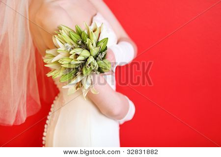 hands of young bride wearing white dress hold bouquet of lilies on red background