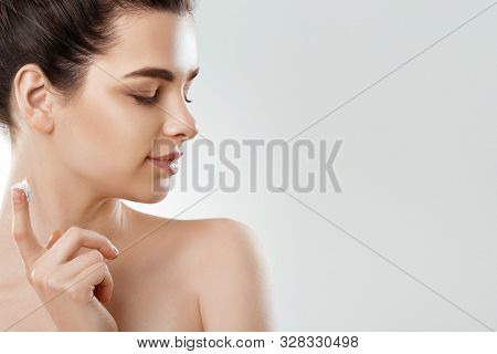Facial Care. Female Applying Cream And Smiling. Beauty Face. Portrait Of Young Woman.  Closeup Of Be