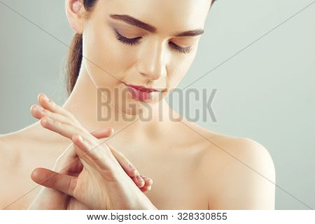 Hand Skin Care. Close Up Of Female Hands Applying Cream, Lotion. Beautiful Woman Hands With Red Mani