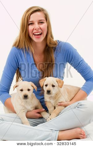 Lovely puppies and happy young girl - portrait of young female with her pet dogs