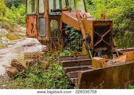 Old, Rusted, Broken Down Bulldozer Sitting On Abandoned Unused Road In Wilderness.