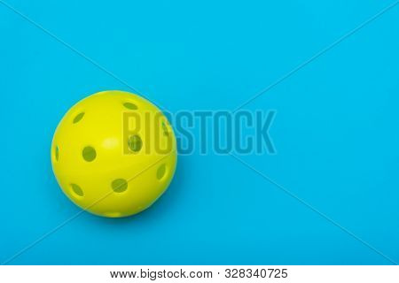 Bright Yellow Pickleball Or Whiffle Ball On A Solid Aqua Blue Flat Lay Background Symbolizing Sports