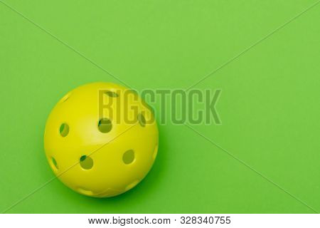 Bright Yellow Pickleball Or Whiffle Ball On A Solid Bright Green Flat Lay Background Symbolizing Spo