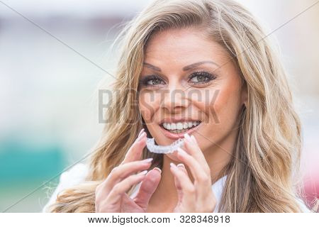 Invisalign Orthodontics Concept - Young Attractive Woman Holding - Using Invisible Braces Or Trainer