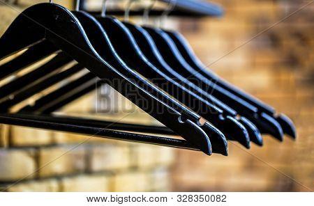 Wood Hangers Coat. Many Wooden Black Hangers On A Rod. Store Concept, Sale, Design, Empty Hangers. W