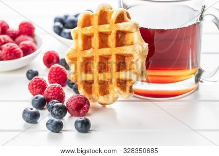 Waffles with blueberries and raspberries. Waffle and tea cup.