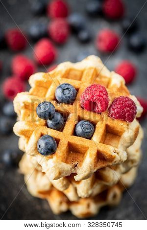 Waffles with blueberries and raspberries on old kitchen table.