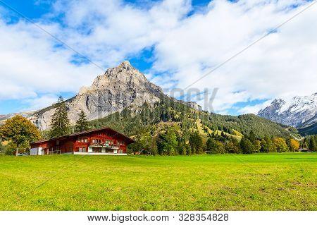 Wooden Chalet In Kandersteg Village, Canton Bern, Switzerland, Europe, Autumn Trees And Mountains Pa