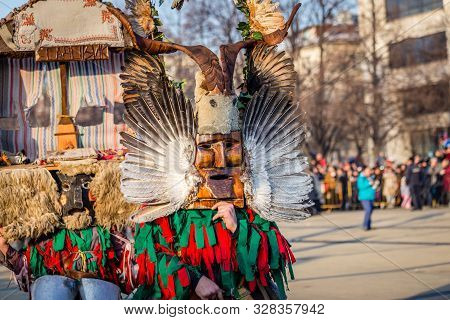 Mummers perform rituals to scare evil spirits at Surva festival at Pernik in Bulgaria. The people with the masks are called Kuker (kukeri). Wood mask with feathers and horns.