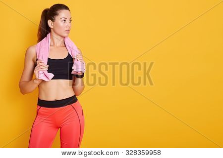 Horizontal Shot Of Spory Woman With Pink Towel On Her Shoulder, Posing Isolated Over Over Yellow Bac
