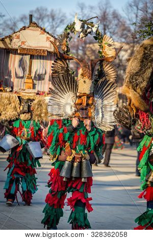 Mummers perform rituals to scare evil spirits at Surva festival at Pernik in Bulgaria. The people with the masks are called Kuker (kukeri). Wood mask with feathers, pigeon.