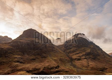Two Of The Three Mountain Peaks Called The Three Sisters, Covered In Brown Wintery Vegetation On A P