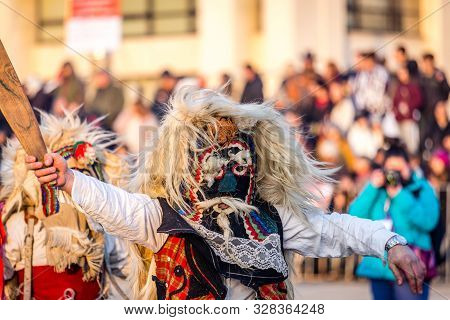 Mummers perform rituals to scare evil spirits at Surva festival at Pernik in Bulgaria. The people with the masks are called Kuker (kukeri). Wool mask and wood sword.