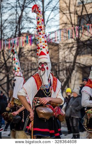 Mummers perform rituals to scare evil spirits at Surva festival at Pernik in Bulgaria. The people with the masks are called Kuker (kukeri). Mask with mustaches.