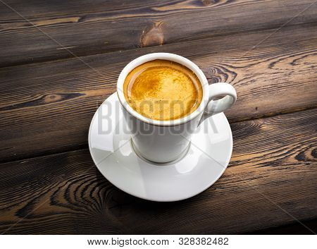 Overhead View Of A Freshly Brewed Mug Of Espresso Coffee On Rustic Wooden Background With Woodgrain