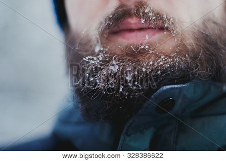 Face Of A Young Bearded Man Frozen In A Blizzard In The Woods. Beard And Mustache Covered With Frost
