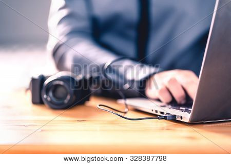 Camera Connected To Laptop With Usb Cable. Man Editing Photos With Computer Software. Photographer T