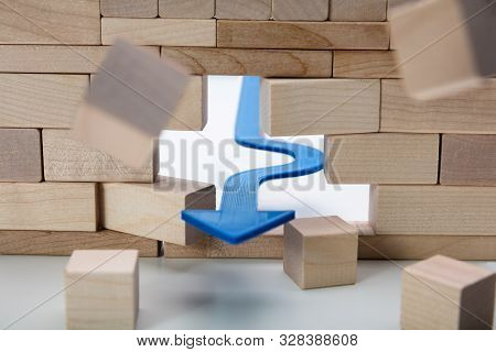 Arrow Breaking Through Wall Made Of Wooden Blocks On White Background