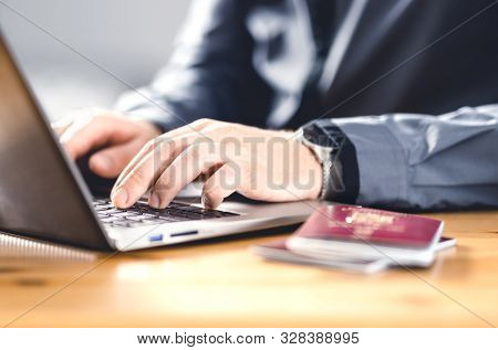 Man With Passport And Laptop. Travel Document And Identification. Immigrant Writing Electronic Appli