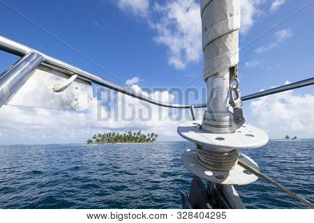 Prow Sail Close Up On The Foreground And Palm Tree Island On The Background At The San Blas Island A