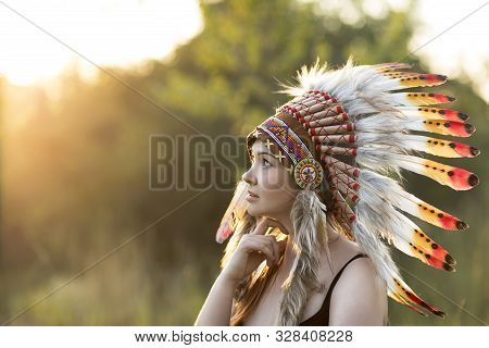 Young Beautiful Girl In A Native American Headdress In Nature During Sunset. American Indian Backgro