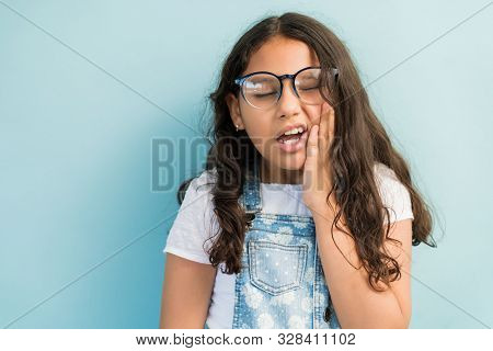 Closeup of female child in discomfort with hand on cheek suffering from toothache in studio poster