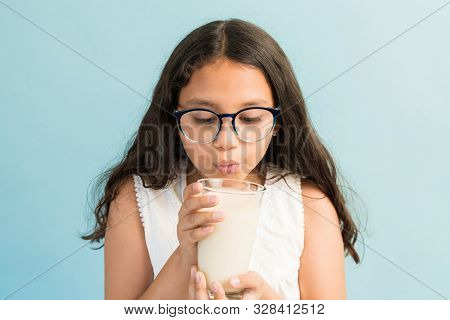 Preadolescent Female Child Blowing On Hot Milk In Glass Against Plain Background