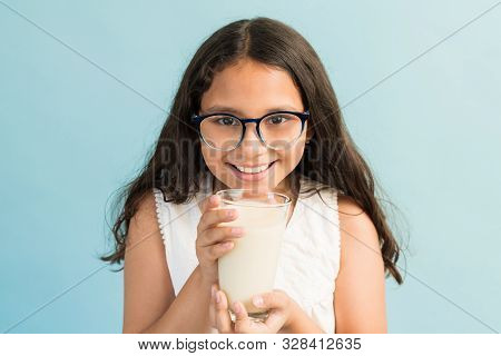 Smiling Hispanic Girl Drinking Fresh Milk From Glass While Making Eye Contact In Studio