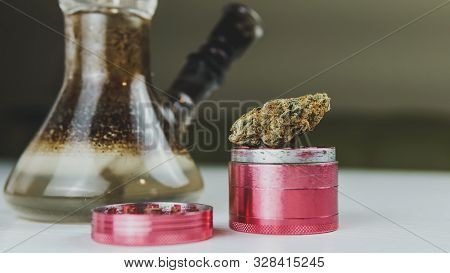 Close-up Of Dirty Bong And Grinder With Medical Marijuana Buds On The White Table. Smoking Cannabis